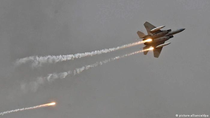 A Saudi F-15 fighter jet releases flares.