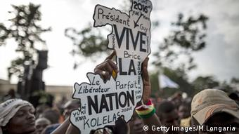 Supporters of opposition presidential candidate Guy Brice Parfait Kolelas carry a cardboard cutout of the country, saying, 'vive la Nation'.