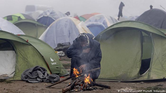 Griechenland Idomeni Flüchtling vor Zelten am Feuer