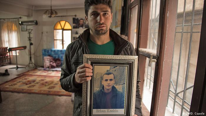 A man holds a portrait of his missing brother in the Dicle Firat Cultural Center