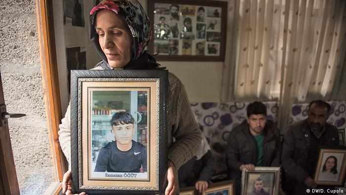 A woman holds a portrait of her missing daughter in the Dicle Firat Cultural Center