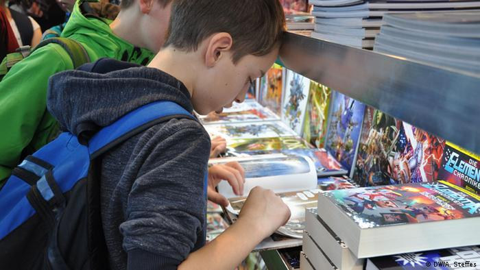 Junge blättert in Comics bei der Comic Con in Leipzig