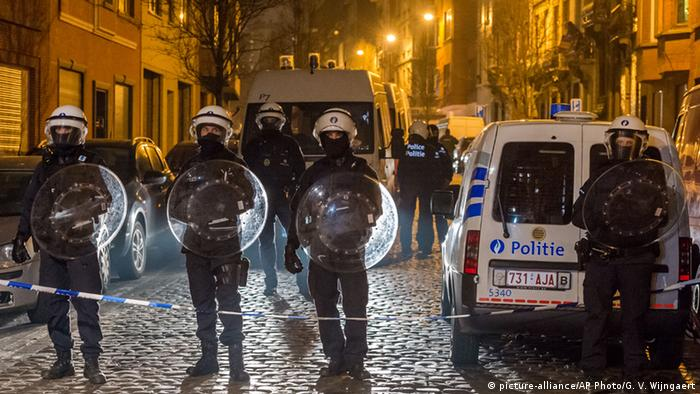 Police officers secure a street during a raid in the Molenbeek neighborhood of Brussels, Belgium (c) picture-alliance/AP Photo/G. V. Wijngaert