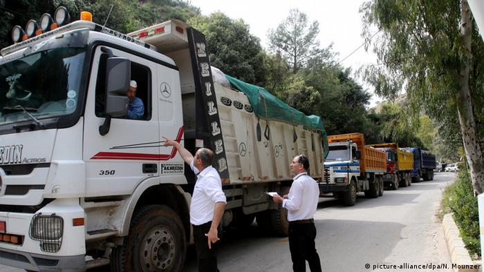 A convoy of trucks carriyng waste from Beirut at the entrance of Al Naemeh landfill in Lebanon