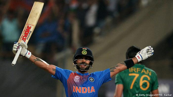 India's Virat Kohli, clutching a bat in his right hand, raises his outstretched arms in victory after securing a win over Pakistan.