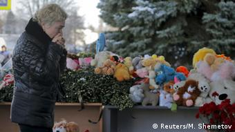A woman reacts while standing near toys and flowers left in memory of the victims REUTERS/Maxim Shemetov