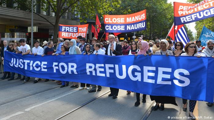 Thousands take to streets to demanding that refugees be given a chance to apply for asylum in australia. In front of the procession, a long banner reads Justice for refugees. Smaller banners in the the background echo that sentiment.