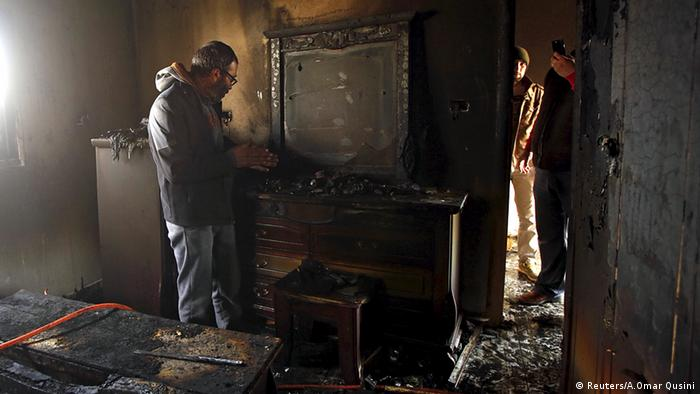 A Palestinian man inspects the damage to the torched house in Duma