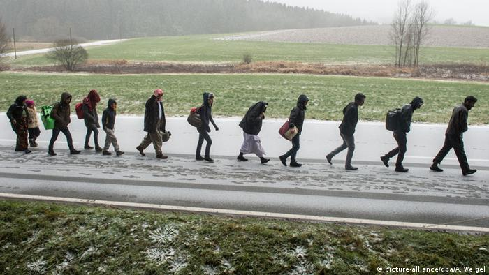 Archive photo from 21.11.2015: Asylum-seekers walk across the German border with Austria in the snow.
