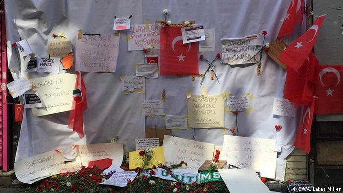 The site of the suicide bombing is bedecked with flowers and signs