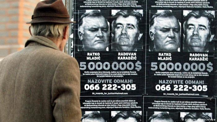 Man looking at Wanted posters for Mladic and Karadzic