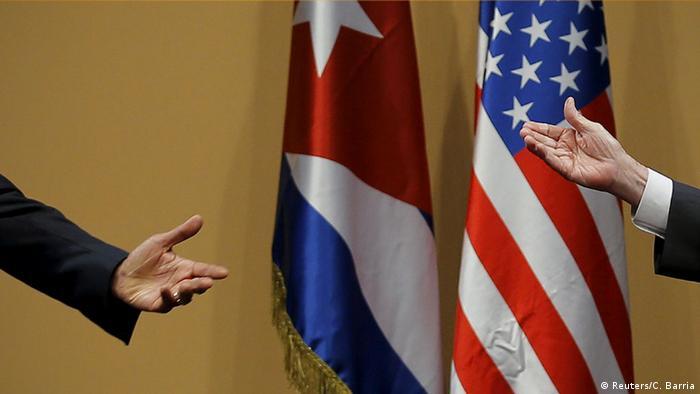 Mãos estendidas de Barack Obama e Raúl Castro diante das bandeiras de Cuba e EUA