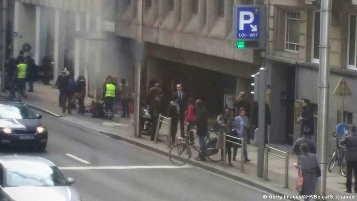 A picture shows Brussels metro travelers exiting the subway as plumes of smoke rise following an explosion