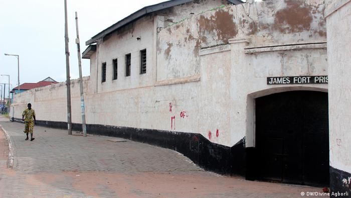 A man walks past the walls of the old James Fort Prison