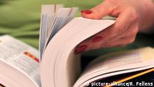 Blättern in einem Wörterbuch © picture-alliance/R. Fellens