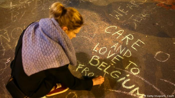 A woman writes a message on the ground as people leave tributes at the Place de la Bourse (Getty Images/C. Court)