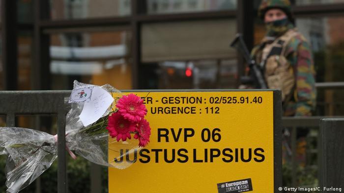 Цветы на табличке в память погибшим в теракте в Брюсселе