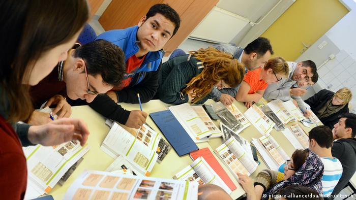 Eine Gruppe von Migrantinnen und Migranten, die in einem Klassenraum an einem langen Tisch sitzen. Im linken Bildrand ist der Kopf einer Lehrerin zu sehen.
