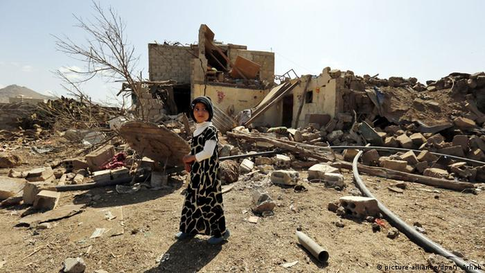 A child walks past her family's house that was destroyed by a Saudi-led airstrike
