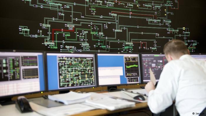 Muškarac za računalima na kojima nadzire dalekovodnu mrežu