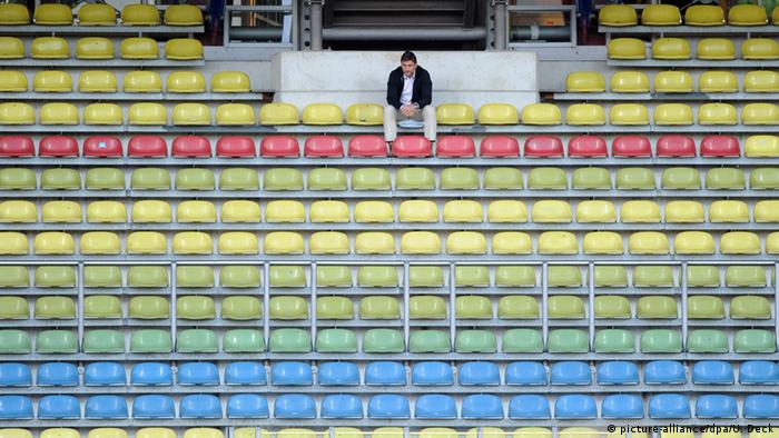 One man sits in an otherwise empty sports stadium (picture-alliance/dpa/U. Deck)