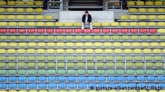 Мужчина сидит на пустой трибуне стадиона