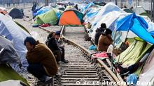 epa05228919 Migrants rest next to their tents at the Greek-Macedonian border, in Idomeni, Greece, 24 March 2016. Migration restrictions along the so-called Balkan route, the main path for migrants and refugees from the Middle East to the EU, has left thousands of migrants trapped in Greece. EPA/ARMANDO BABANI +++(c) dpa - Bildfunk+++