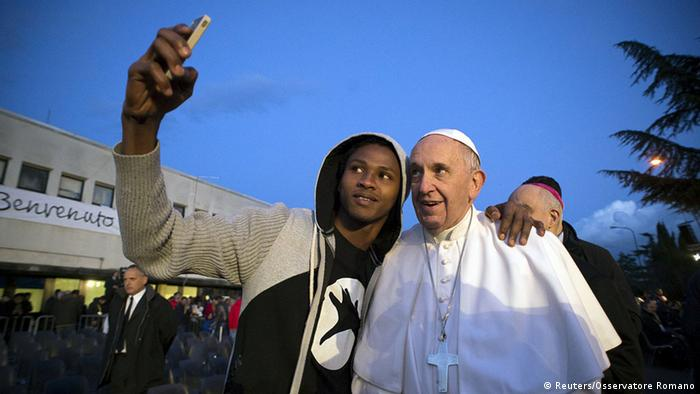 Pope Francis in a selfie with a refugee in a migrant center near Rome. The pontiff may travel to Lesbos