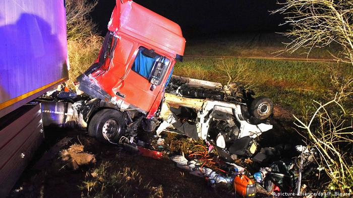 The cab of a tractor-trailer is pressed into the mangled remains of a minibus in a ditch on the side of the road.