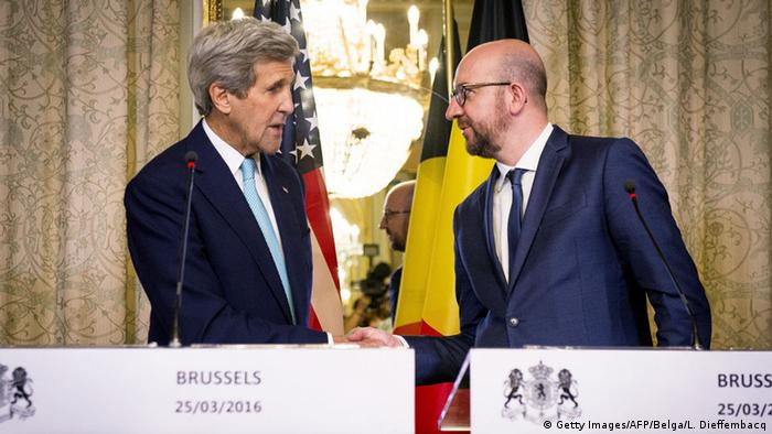 US Secretary of State John Kerry and Belgian Prime Minister Charles Michel shake hands while standing behind their respective lecturns.