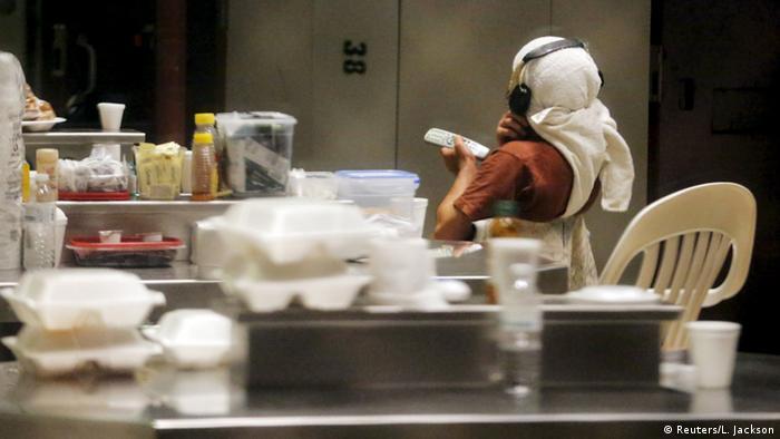 Заключенный Гуантанамо смотрит телевизор. На переднем плане - упаковки с едой