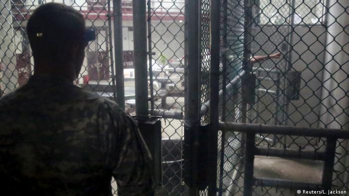 Охранник лагеря Гуантанамо, снятый со спины. Через решетку он наблюдает за происходящим в соседних помещениях