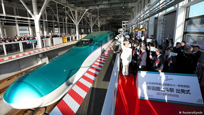 Participants wave flags during a ceremony to see off the first high speed train from Hokkaido to Tokyo.