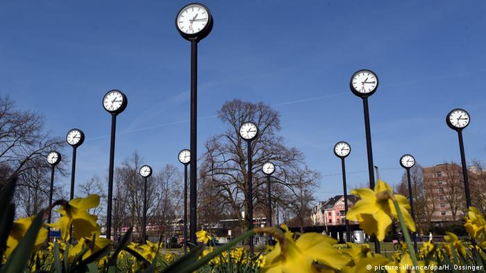 Many tall-standing clock-towers above plants outside, blue sky in the background (Copyright: picture-alliance/dpa/H. Ossinger
