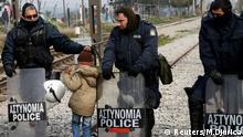 A migrant boy walks past Greek police at a makeshift camp at the Greek-Macedonian border near the village of Idomeni, Greece, March 27, 2016. REUTERS/Marko Djurica © Reuters/M.Djurica