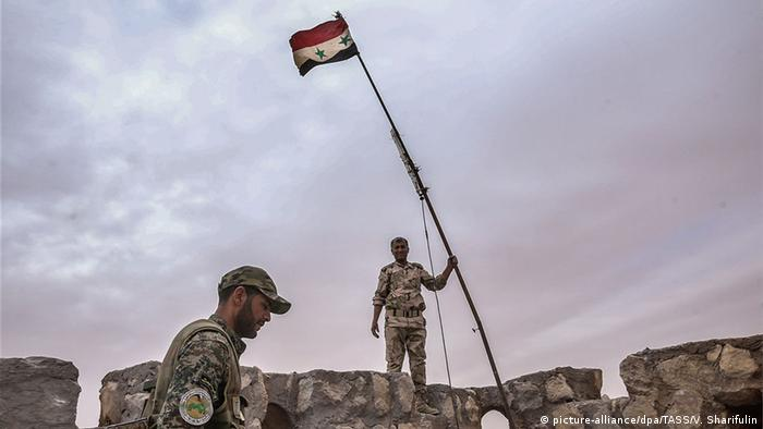 Government troops raise the Syrian flag in Palmyra