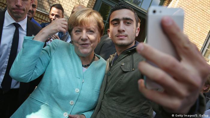 Ангела Меркель 9 сентября 2015 года фотографируется в Берлине с сирийским беженцем Анасом Модамани