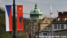 26.03.2016 *** A Czech National flag hangs next to a Chinese National flag splattered with a black substance in Prague on March 26, 2016 Dozens of Chinese flags that had been hung up in the streets of Prague ahead of a landmark visit by Chinese President Xi Jinping were defaced overnight police said. / AFP / Michal Cizek (Photo credit should read MICHAL CIZEK/AFP/Getty Images) © Getty Images/AFP/M. Cizek