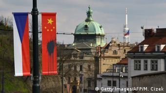 Chinese flag sprayed with black substance next to Czech flag