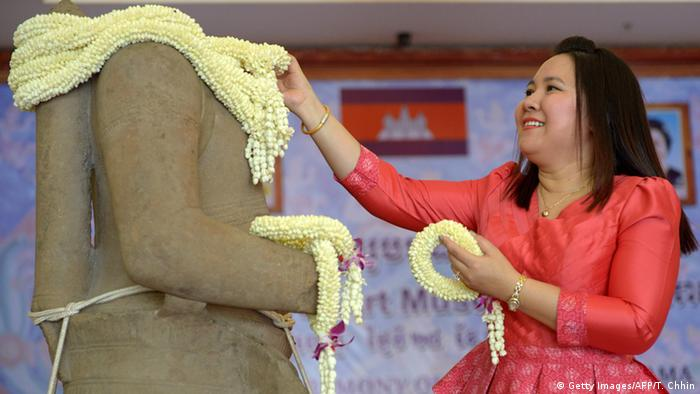 A Cambodian woman places a garland around a 10th-century sandstone sculpture of the Hindu god Rama after it was returned from the Denver Art Museum