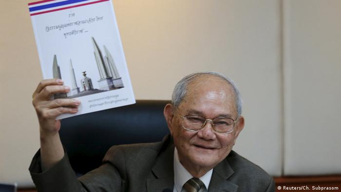 Meechai Ruchupan, head of Thailand's Constitution Drafting Committee, holds up a draft constitution during a news conference at the parliament in Bangkok, Thailand
