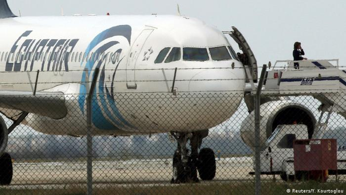 An official telephones from the ramp of a hijacked Egyptair A320 Airbus at Larnaca Airport in Larnaca, Cyprus.