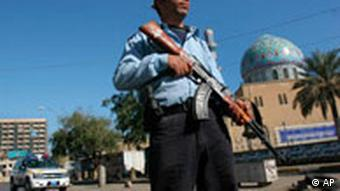 An Iraqi policeman stands guard next to a Sunni mosque in Baghdad