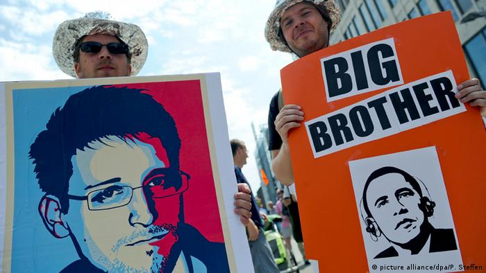 Protestors holding pictures of Edward Snowden and President Obama (Photo: picture alliance/dpa/P. Steffen)