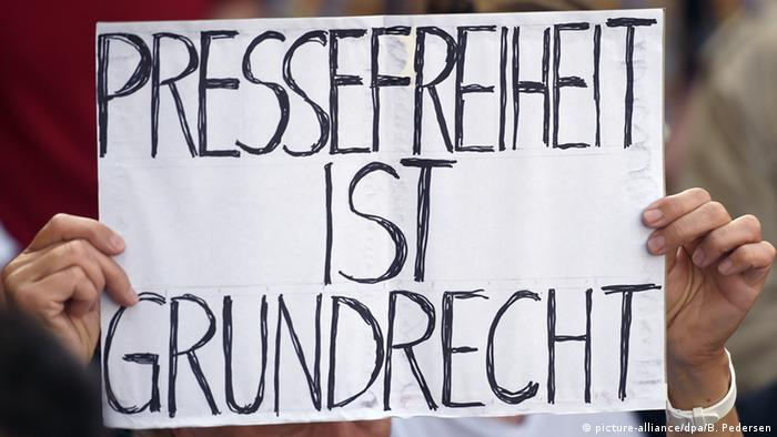 A protester in Berlin holding a sign that says: Press freedom is a fundamental right