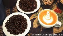 Ein Cappuccino mit einem Muster aus Herzen ist am 03.03.2016 in Rottendorf (Bayern) bei Würzburg neben frischen Kaffeebohnen zu sehen. Der Würzburger Daniel Gerlach (27) ist Deutscher Latte Art Meister 2015. Ende März tritt er bei der WM in Shanghai an. Foto: Nicolas Armer/dpa (zu dpa-KORR Der Schwanenkönig malt Gemälde in den Kaffee Wiederholung vom 22.03.2016) +++(c) dpa - Bildfunk+++ © picture-alliance/dpa/N.Armer