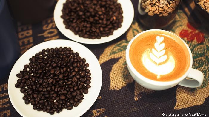 Xícara de Capucino com dois Pratos de grãos de café.