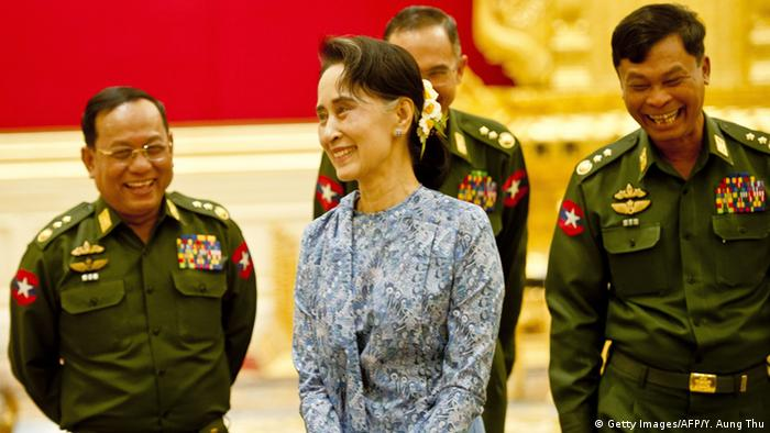 Newly sworn in Myanmar Foreign Minister Aung San Suu Kyi (C) and a military general share a light momemt during the handover ceremony at the presidential palace in Naypyidaw on March 30, 2016