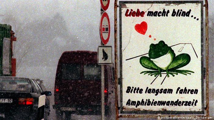 Autos neben einem Warnschild mit der Aufschrift: Liebe macht blind. Bitte langsam fahren. Amphibienwanderzeit (picture-alliance/dpa/V. Dornberger)