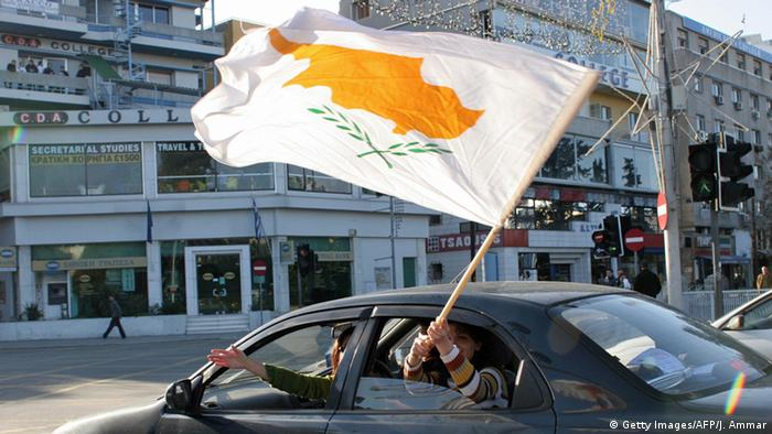 Cypriots drive through the capital, Nicosia, waving a large white flag with a map of the island, in yellow.
